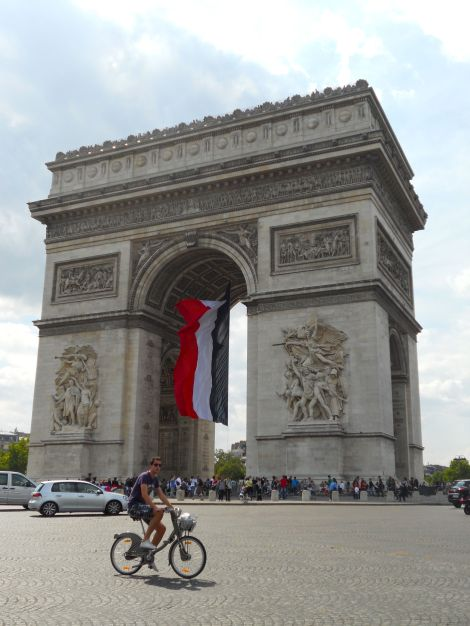 Not quite the Tour de France, a Vélib cyclist makes his way around the Arc de Triomphe