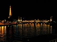 The lights of the Eiffel Tower and the Pont Alexandre III shimmer on the Seine.