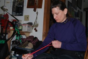 Laura weaves the dogs' nylon neck lines.