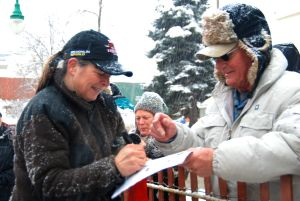 Jan signs the Iditarod program of an eager fan.