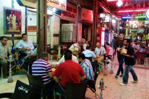 Egyptian gentlemen gather, as they so often do, for a game of backgammon or dominoes, social time, and hookah smoke.