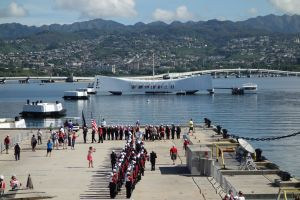 With the USS Arizona Memorial in the background, a high school band performs a medley of patriotic songs at their visit to the USS Missouri.