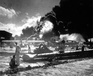 Sailors watch as the USS Shaws burns in the background of destroyed planes on Ford Island.