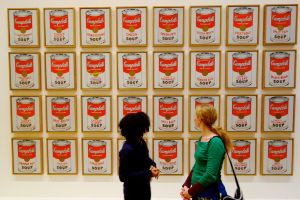 Campbell's Soup Cans by Andy Warhol invites us to reflect on sentiment, comfort, mass production, and mass consumption.