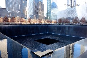 Sheets of water fall endlessly into one of the square pools where the Twin Towers once stood.