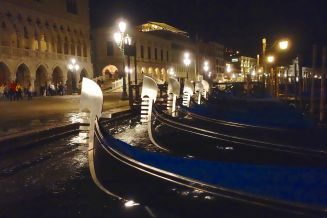 A chorus line of empty gondole bob energetically on the high waters of Venice.