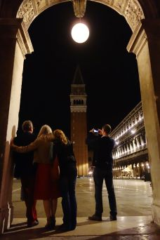 A family enjoys a moment together under the arches of Piazza San Marco.