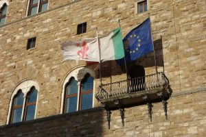 The flags of Florence, Italy, and the European Union adorn the facade of the Palazzo Vecchio on the Piazza della Signoria.